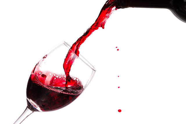 Red wine being poured into wine glass isolated with splash on the white