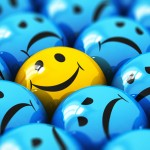 Single happy yellow smiley among blue sad ones