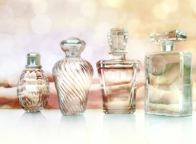 Different bottles of perfume on lighte background.